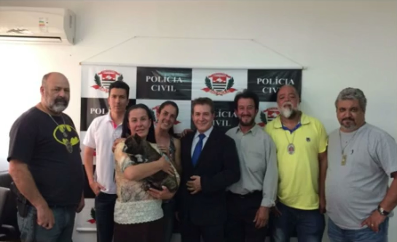 equipe de policiais com a vitima e seu cachorro